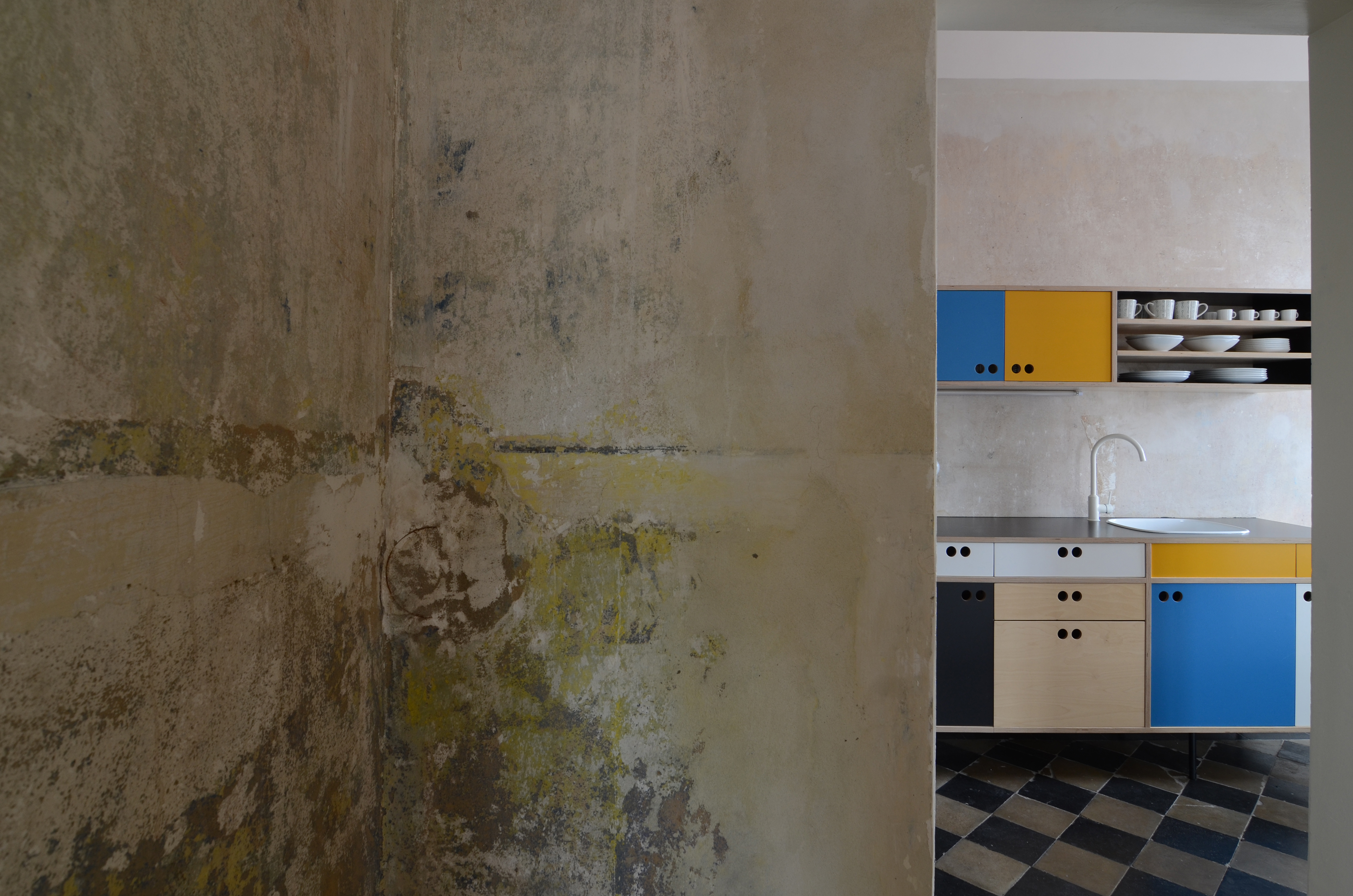 View of the stripped wall and blue and yellow kitchen