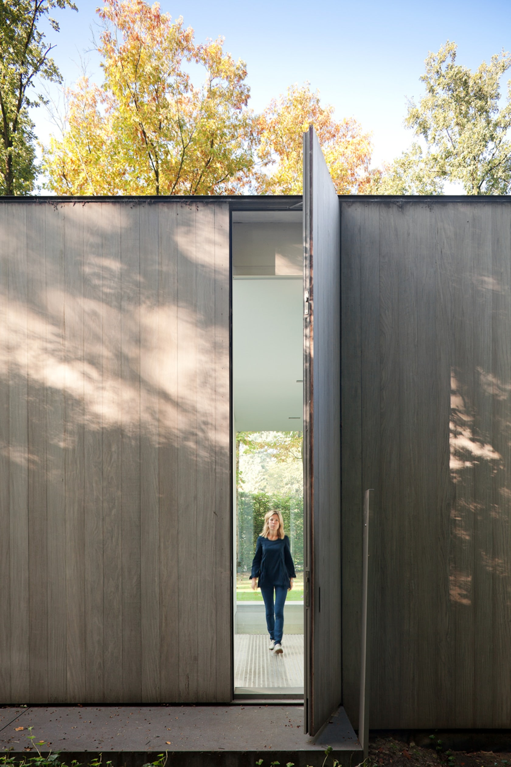 ... Full Height Door Into The Façade Of This Largely Glass Clad Home In  Belgium. The Pivoting Door Matches The Gray Timber Paneling That Lines The  Exterior.