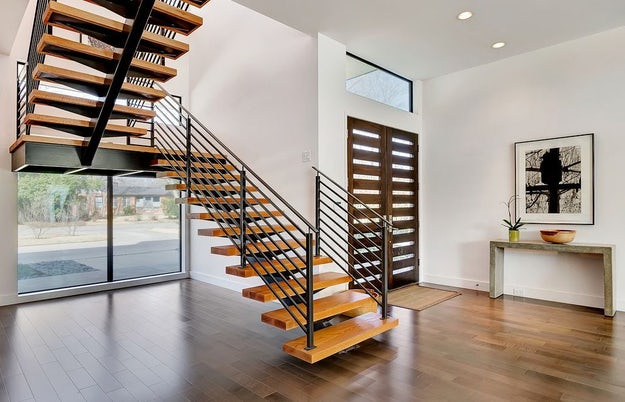 Mono-stringer floating staircases with metal railing and spindles; Image  via Eva Furniture