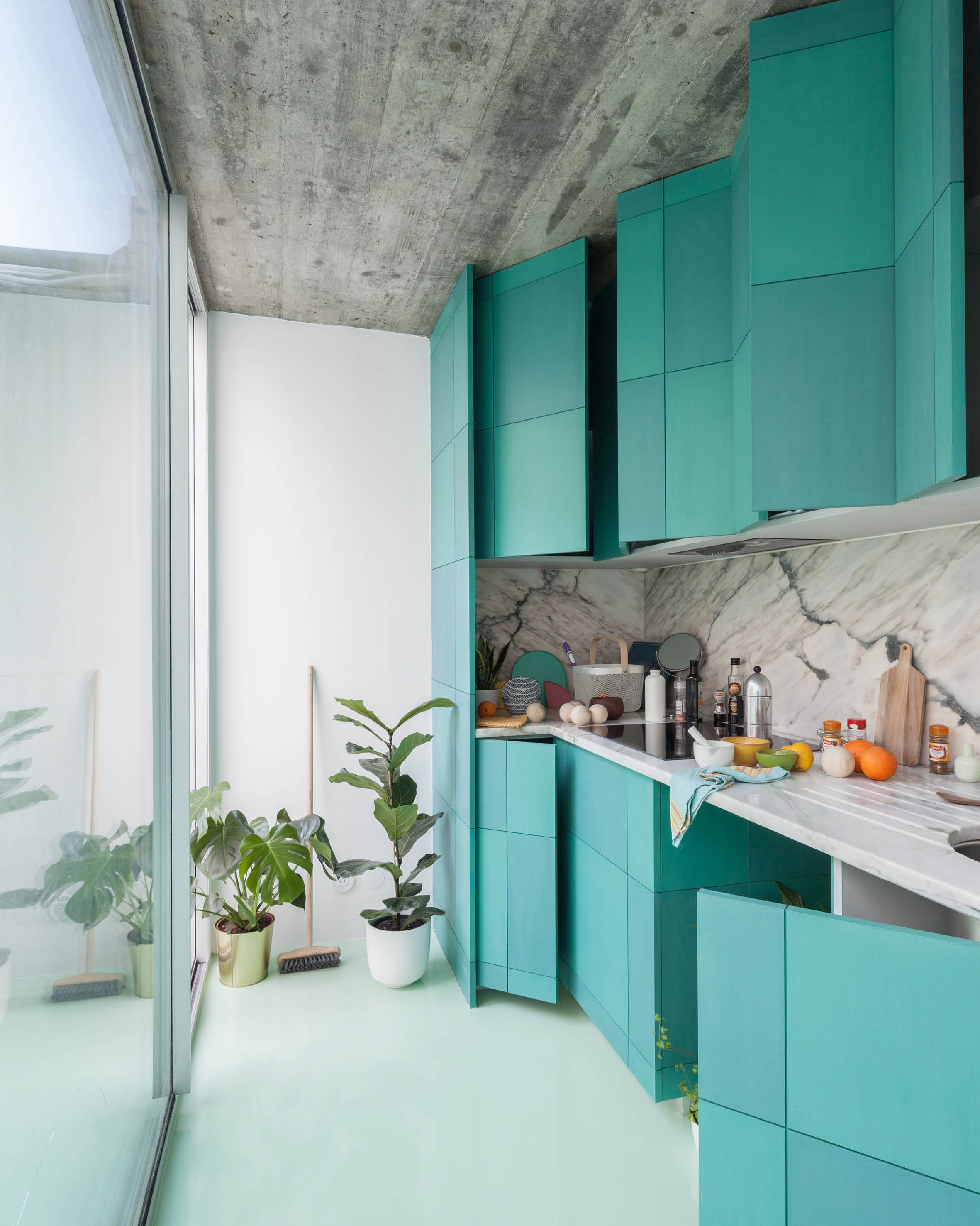Mint floor and shades of green cabinetry in a kitchen by fala atelier